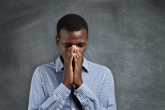 Jonge afrikaanse man hand in hand in gebed, probeert te kalmeren, denkend aan iets slechts, het beste van hopen.