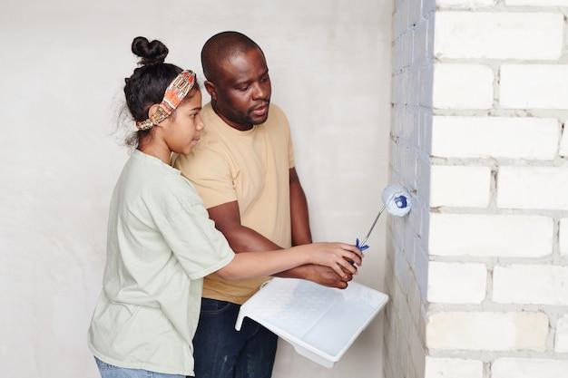 Jonge afrikaanse man helpt zijn schattige dochter met verfroller die de bakstenen muur van de woonkamer in witte kleur schildert terwijl hij in de hoek staat