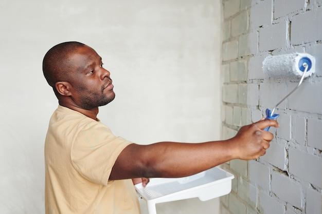 Jonge afrikaanse man in beige t-shirt met verfroller terwijl hij voor de bakstenen muur van de woonkamer staat en deze in witte kleur schildert