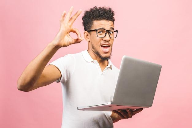 Jonge afrikaanse man in casual bedrijf scherm laptop computer terwijl ok teken gebaar wordt weergegeven