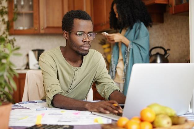 Jonge afrikaanse man in glazen zit open laptop, geconcentreerd op papierwerk, binnenlandse rekeningen online betalen