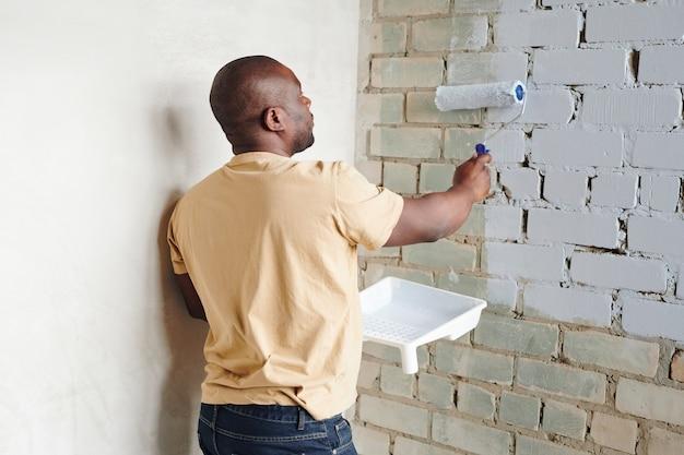 Jonge afrikaanse man in vrijetijdskleding die een verfroller vasthoudt terwijl hij bij de hoek voor een bakstenen muur staat en deze in een witte kleur schildert