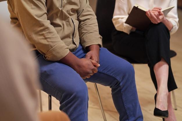Jonge afrikaanse man in vrijetijdskleding zittend op een stoel tijdens psychologische sessie
