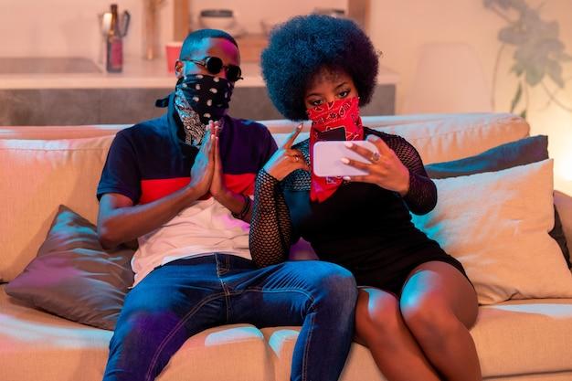 Jonge afrikaanse man in zwarte gezicht bandana handen bij elkaar houden door de borst zittend naast meisje met rode nikab selfie maken