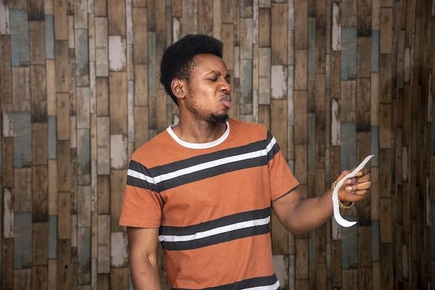 Jonge afrikaanse man kijkt naar een stuk papier