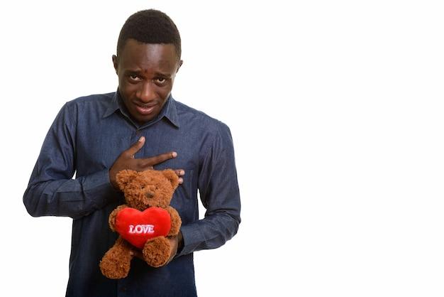 Jonge afrikaanse man kijkt verdrietig terwijl hij teddybeer vasthoudt