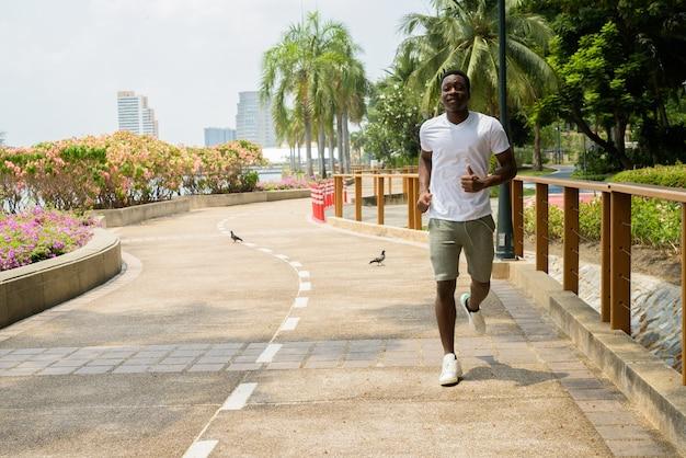 Jonge afrikaanse man loopt buiten in het park