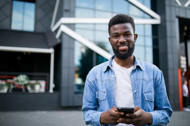 Jonge afrikaanse man lopen op straat gebruik telefoon