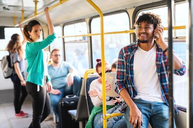 Jonge afrikaanse man luisteren naar de muziek tijdens het rijden in het openbaar vervoer.