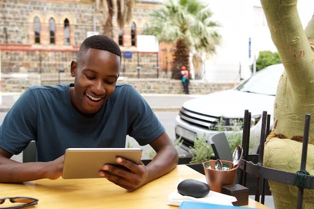 Jonge afrikaanse man met behulp van digitale tablet in een café