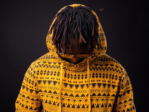 Jonge afrikaanse man met dreadlocks op zwart