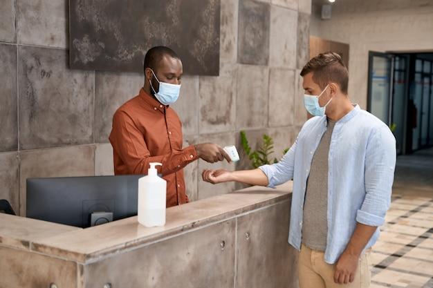Jonge afrikaanse man met een medisch masker die bij de receptie in het moderne kantoor staat en meet