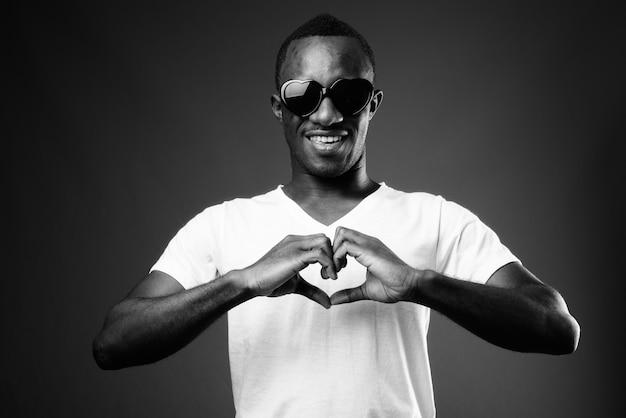 Jonge afrikaanse man met een zonnebril terwijl het hart ondertekenen