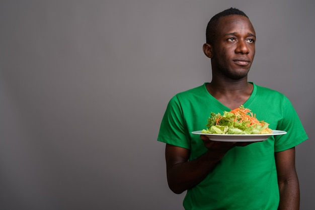 Jonge afrikaanse man met groen shirt op grijze muur