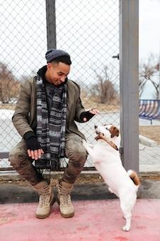 Jonge afrikaanse man met muts en sjaal wandelen met hond.