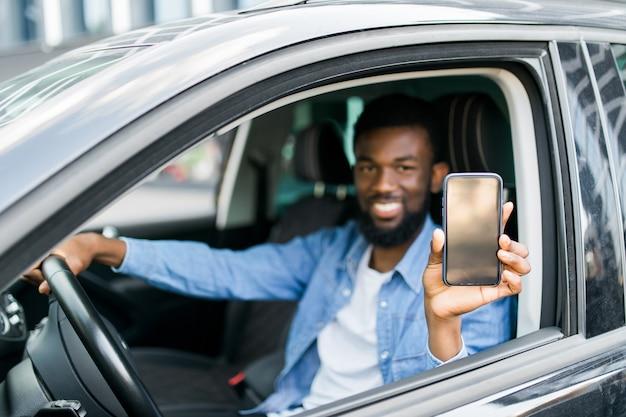 Jonge afrikaanse man met telefoon met scherm zittend in zijn auto. kopieer ruimte.