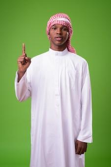 Jonge afrikaanse man met traditionele islamitische kleding tegen een groene achtergrond