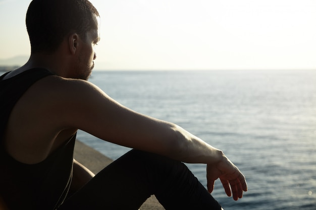 Jonge afrikaanse man overweegt verbazingwekkende landschap van kalme zee