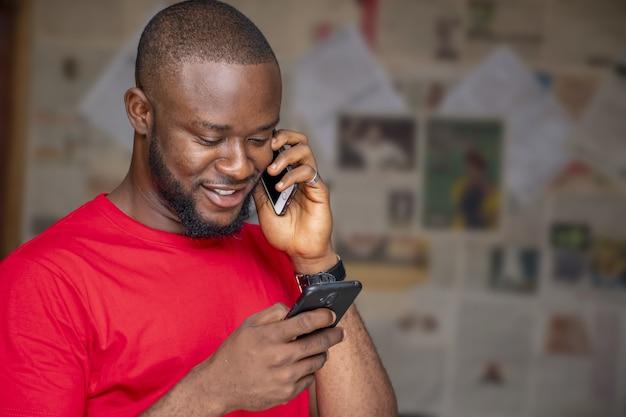 Jonge afrikaanse man praten aan de telefoon tijdens het gebruik van een andere in een kamer