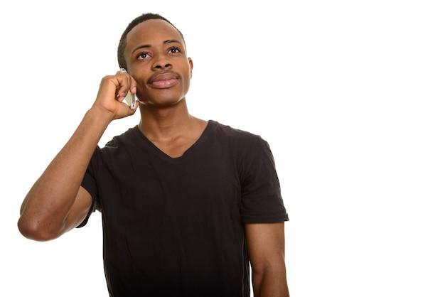 Jonge afrikaanse man praten over de mobiele telefoon tijdens het denken