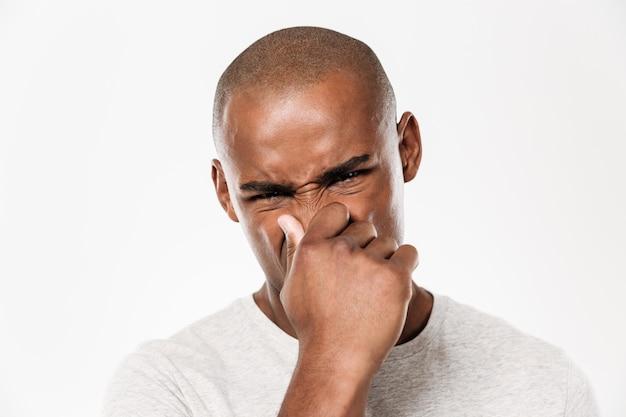 Jonge afrikaanse man sluit een neus van een stank.