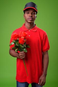 Jonge afrikaanse man tegen groene muur