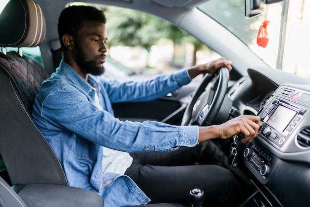 Jonge afrikaanse man verandert muziek in de auto tijdens het rijden op de weg