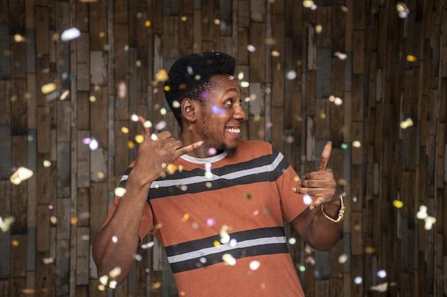 Jonge afrikaanse man viert feest met rondzwevende confetti