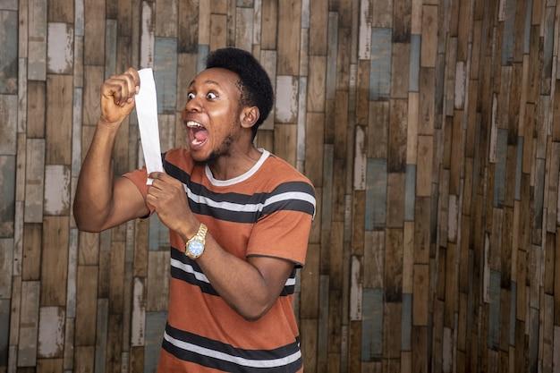 Jonge afrikaanse man voelt zich opgewonden en gelukkig terwijl hij een papieren strookje vasthoudt en er vreugdevol tegen schreeuwt