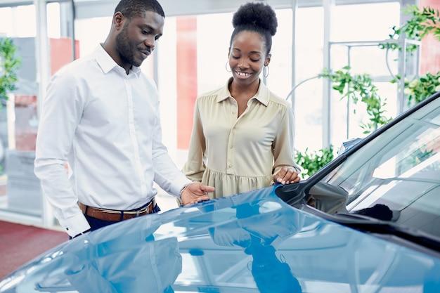 Jonge afrikaanse man vraagt de mening van zijn vrouw over auto bij dealer
