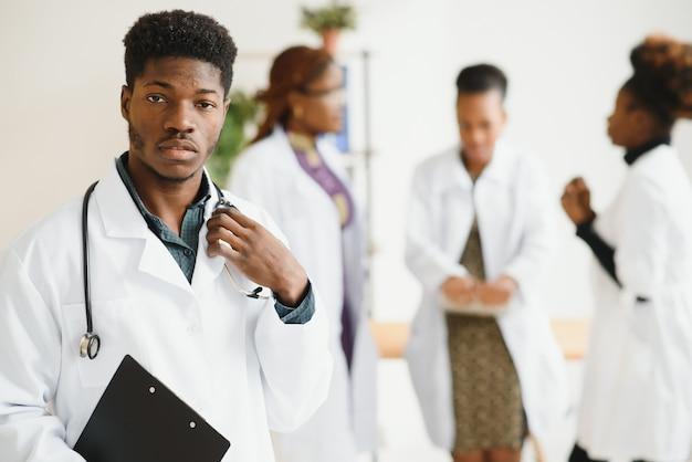 Jonge afrikaanse mannelijke arts die terwijl status in een het ziekenhuisgang glimlacht met een diverse groep van personeel op de achtergrond