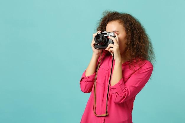 Jonge afrikaanse meisje in casual kleding fotograferen op retro vintage fotocamera geïsoleerd op blauwe turquoise muur achtergrond in studio. mensen oprechte emoties levensstijl concept. bespotten kopie ruimte.