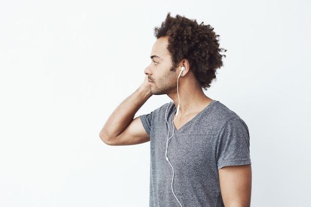 Jonge afrikaanse mens die in hoofdtelefoons in kant kijkt. profiel.
