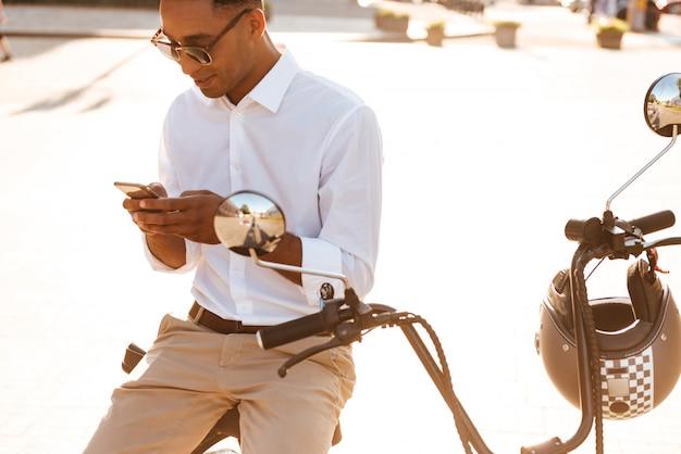 Jonge afrikaanse mens die in zonnebril op moderne motor in openlucht zitten en smartphone gebruiken