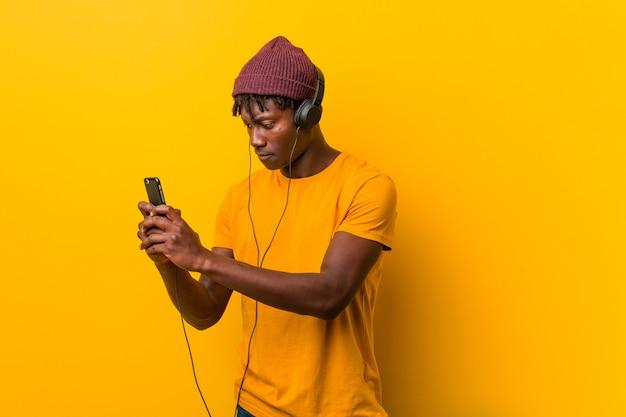 Jonge afrikaanse mens die zich tegen een geel bevindt die een hoed draagt die aan muziek met een telefoon luistert