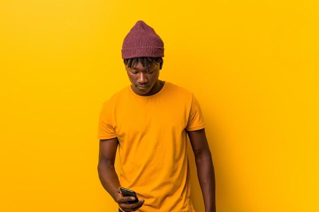 Jonge afrikaanse mens die zich tegen een geel bevindt die een hoed draagt en een telefoon met behulp van