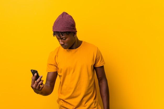Jonge afrikaanse mens die zich tegen een gele achtergrond bevindt die een hoed draagt en een telefoon met behulp van