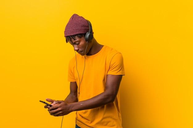 Jonge afrikaanse mens die zich tegen een gele muur bevindt die een hoed draagt die aan muziek met een telefoon luistert
