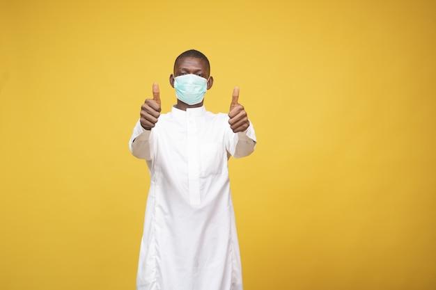 Jonge afrikaanse moslimman die een gezichtsmasker draagt en zijn duimen omhoog houdt