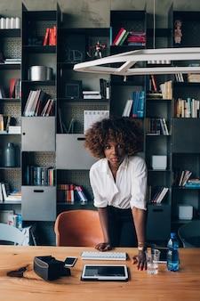 Jonge afrikaanse onderneemster die in mede-werkt bureau werken en camera kijken