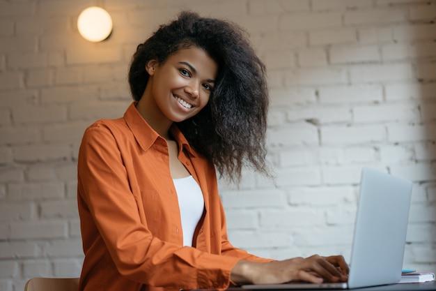 Jonge afrikaanse ontwerper die laptop met behulp van, die van huis werken