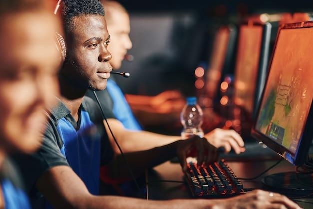 Jonge afrikaanse professionele cybersport-gamer die een koptelefoon draagt die online videogame speelt terwijl