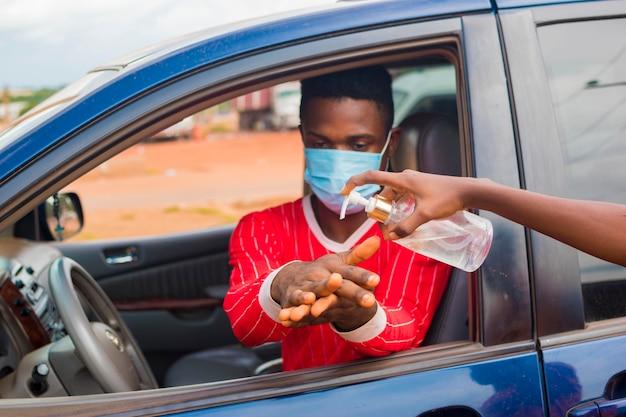 Jonge afrikaanse taxichauffeur die gezichtsmasker draagt, voorkomt, voorkomt, verhindert dat hij uitbreekt in de samenleving en gebruikt handdesinfecterend middel om zijn handen te wassen