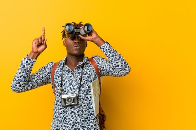 Jonge afrikaanse toeristenmens die zich op geel bevindt die verrekijkers houdt