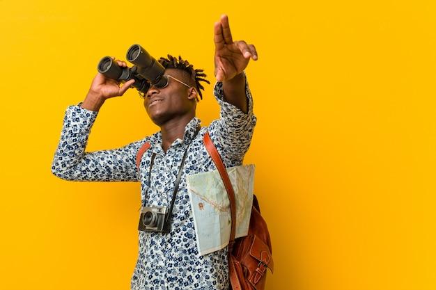 Jonge afrikaanse toeristenmens die zich tegen een gele achtergrond bevindt die verrekijkers houdt