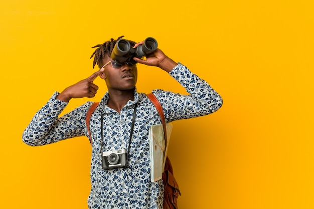 Jonge afrikaanse toeristenmens die zich tegen een gele muur bevindt die verrekijkers houdt