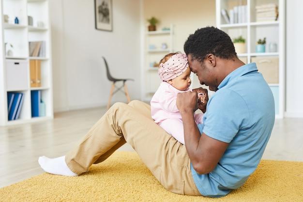 Jonge afrikaanse vader zittend op de vloer en spelen met zijn dochtertje in de kamer thuis