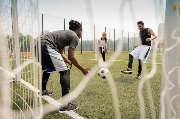 Jonge afrikaanse voetballer die de bal vangt terwijl zijn rivaal het tijdens spel op het gebied schopt
