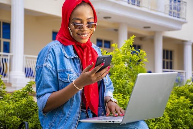 Jonge afrikaanse vrouw aan het werk terwijl ze met haar laptop in een park zit