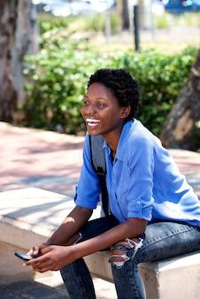 Jonge afrikaanse vrouw die buiten met celtelefoon lacht
